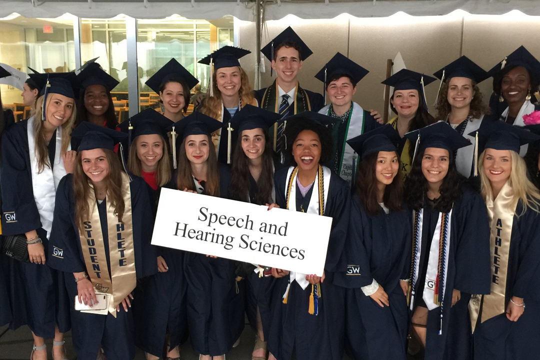 "A group of graduating students in their caps and gowns holding a sign that says ""Speech and Hearing Sciences."""
