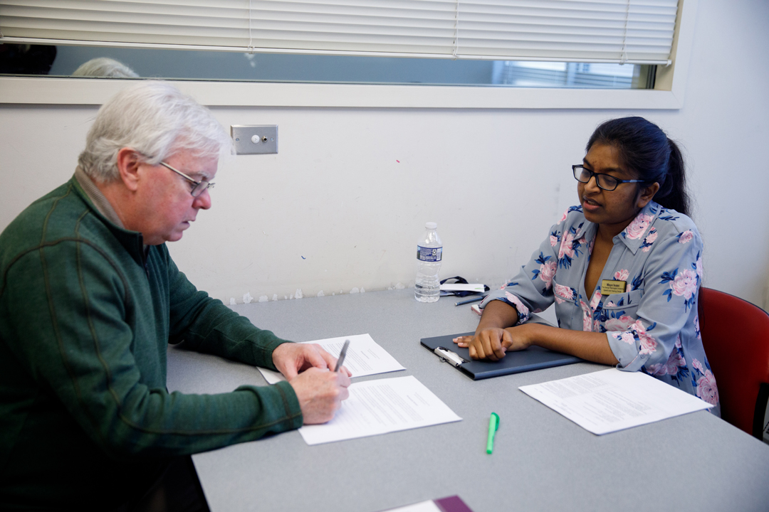 Speech and Hearing student seated at a table working with a patient.
