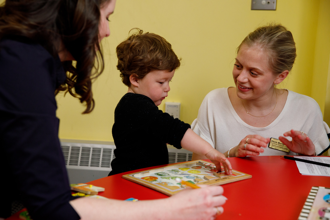 Two Speech and Hearing graduate students work with a toddler.