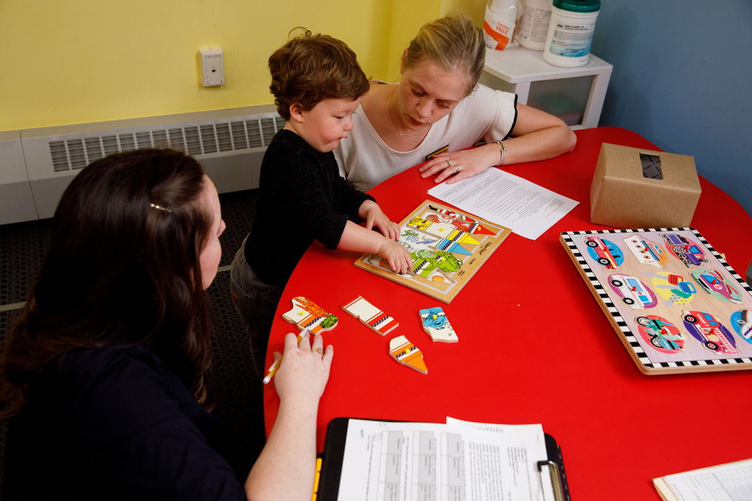 Two Speech and Hearing students work with a toddler who is doing a puzzle.