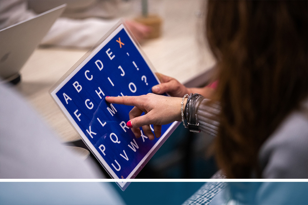 During an exercise in autism treatment, a woman's hand pointing at a board printed with letters of the alphabet