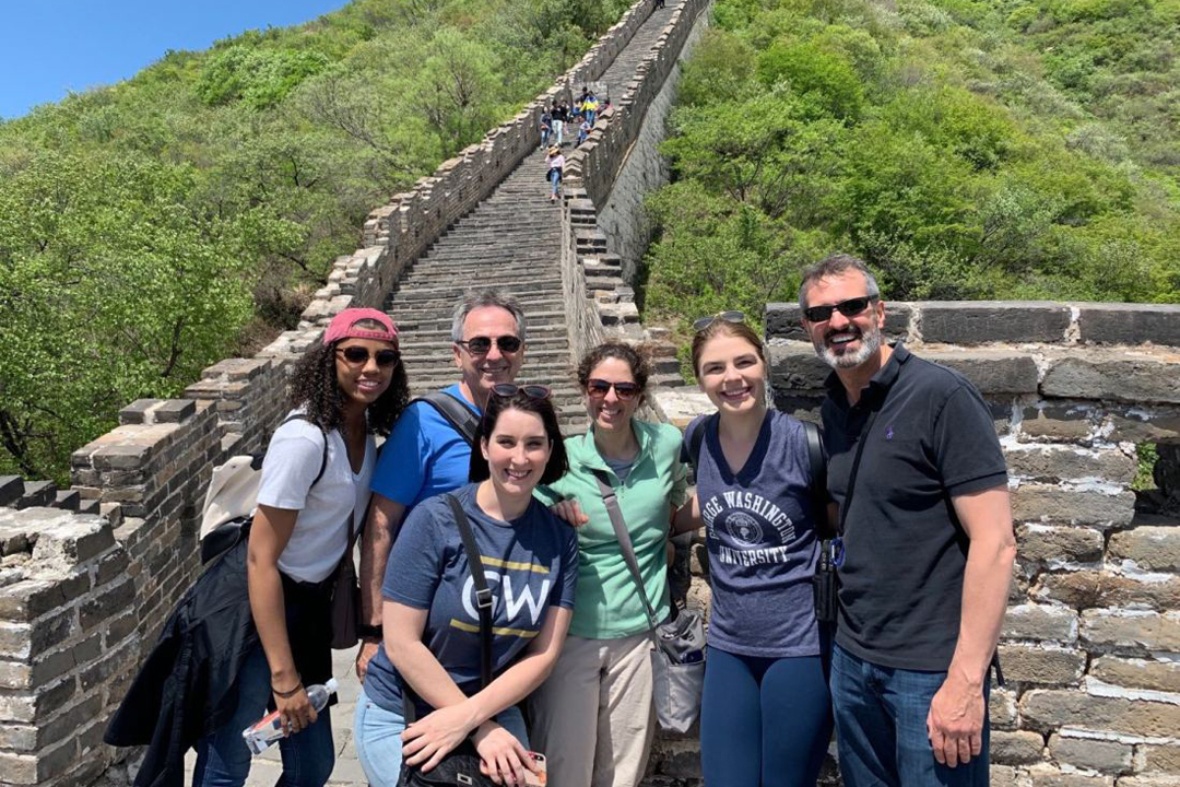 Group of speech and hearing students and faculty members in front of the Great Wall of China.