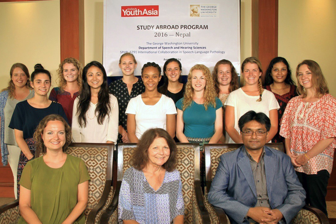 Department of Speech and Hearing Sciences participants smiling in front of a banner that says Study Abroad Program, 2016—Nepal.