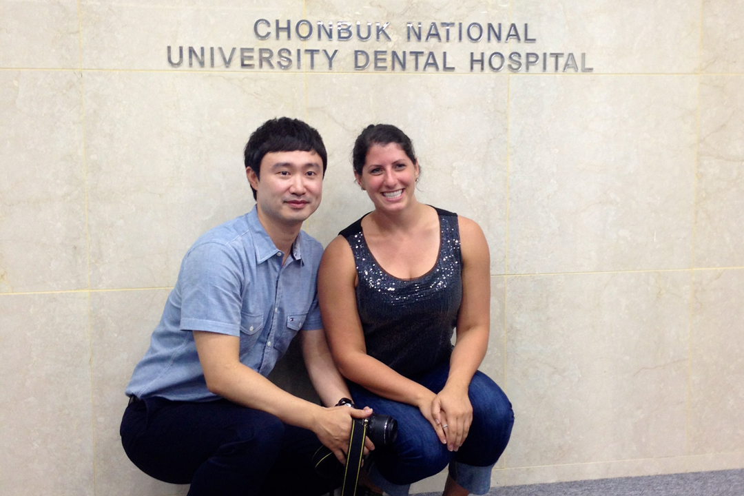 Two people smiling in front of a sign for the Chonbuk National University Dental Hospital.