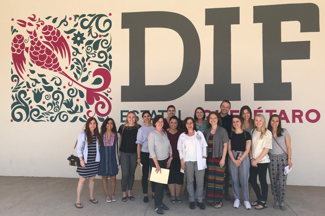 Group of graduate students and faculty in front of a DIF sign in Mexico during a study abroad trip.