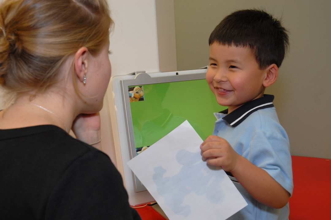 Speech and Hearing student works with a child who is holding a sheet of paper.